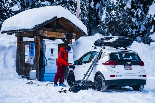 Greg Hill putting his electric car on charging before ski touring at Rogers Pass, British Columbia, Canada.